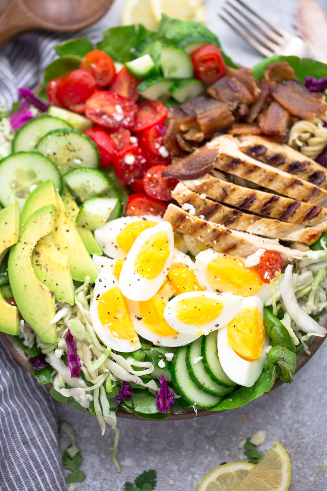 Close up view of Cobb Salad with grilled chicken in a bowl on a grey background with lemon slices