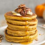 Side view of 5 stacked pumpkin pancakes on a white plate